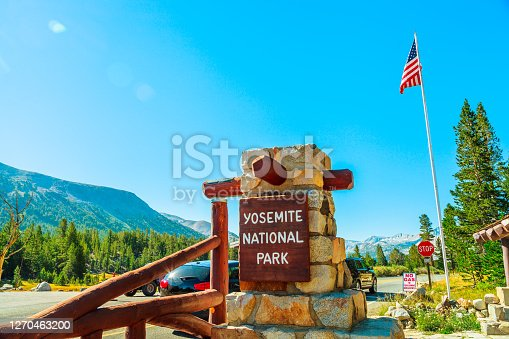 Entrance gate with American flag of Yosemite National Park. Summer American holidays in California of United States of America.