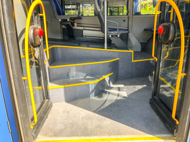 Entrance glass door with handrail and steps in the city bus. Close up shot stock photo