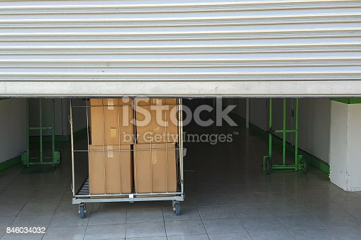 istock Entrance into self storage units, big cart with boxes in front, metal gate 846034032