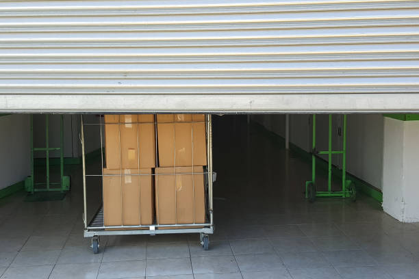 Entrance into self storage units, big cart with boxes in front, metal gate - foto stock