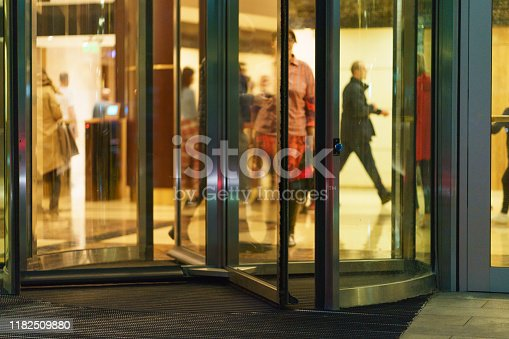 Photography of entrance into the modern Business Center with revolving door in sunset. Image through window glass.