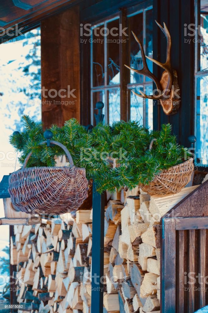 Entrance of a farmhouse with firewood and antlers stock photo
