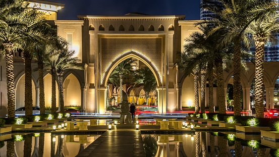 Arch, Entrance of Hotels, offices and Souk near Burj Khalifa the tallest building in the world night timelapse hyperlapse in Dubai, UAE Palms and reflections in water of fountain pool