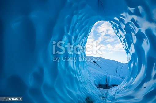Large egg-shaped tunnel inside the ice of the Matanuska Glacier. The ice is a deep blue in the early morning hours after a night out in the Alaskan Wilderness.