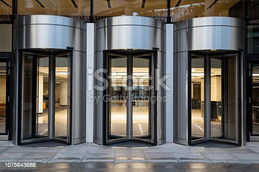 Glass-fronted office building entrance at dusk with revolving doors, London, United Kingdom