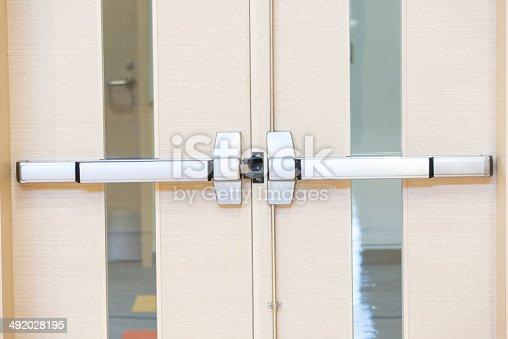 Unlocked metal latch on wooden door.