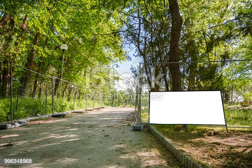 istock entrance to a construction site in a forest with white billboard for you advertising. 996348968