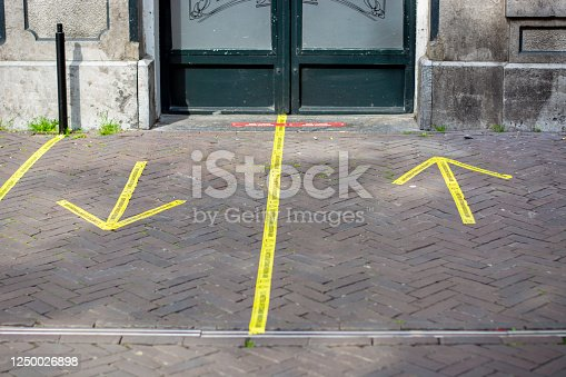 521911567 istock photo Entrance to a pub with yellow sticker tape reminding people in Dutch to keep social distancing 1250026898