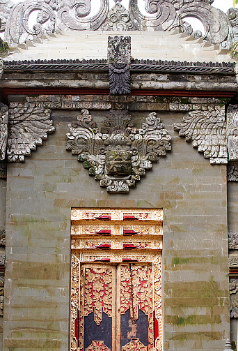 Bali, Indonesia - February 14, 2017: Colour photograph of a golden door /  entrance to an Indonesian Temple in Bali. The entrance is decorated with stone carvings.