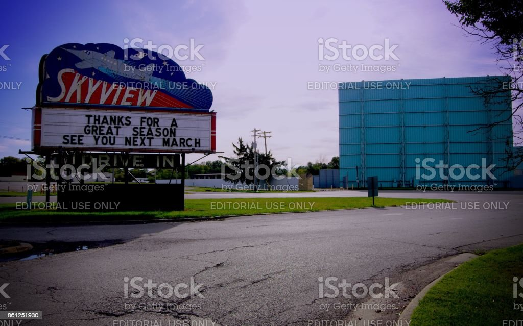 Entrance to drive-in theater sign with rocket ship stands in front of main movie screen. royalty-free stock photo