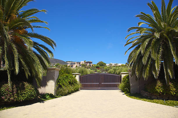 Entrance to Malibu Home Entrance to large home in Malibu, California with large date palms on either side of large wooden driveway sliding door; turn around and one can see the ocean; has view to luxury home up on hillside overlooking the ocean view gated community stock pictures, royalty-free photos & images