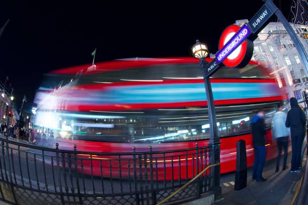 Entrance to Piccadilly Circus Underground Station, London Long exposure view of the iconic London Underground roundel at night, with London bus. skeable stock pictures, royalty-free photos & images