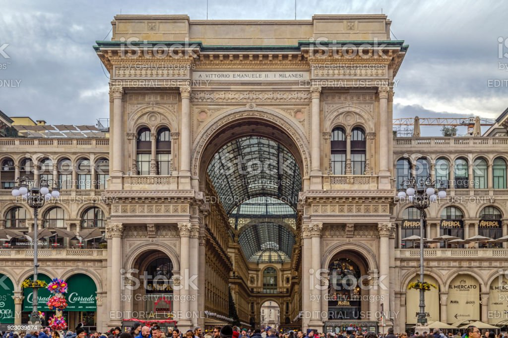 Entrance to the Vittorio Emanuele II Galleries in Dome Square at Milan, full with tourists stock photo