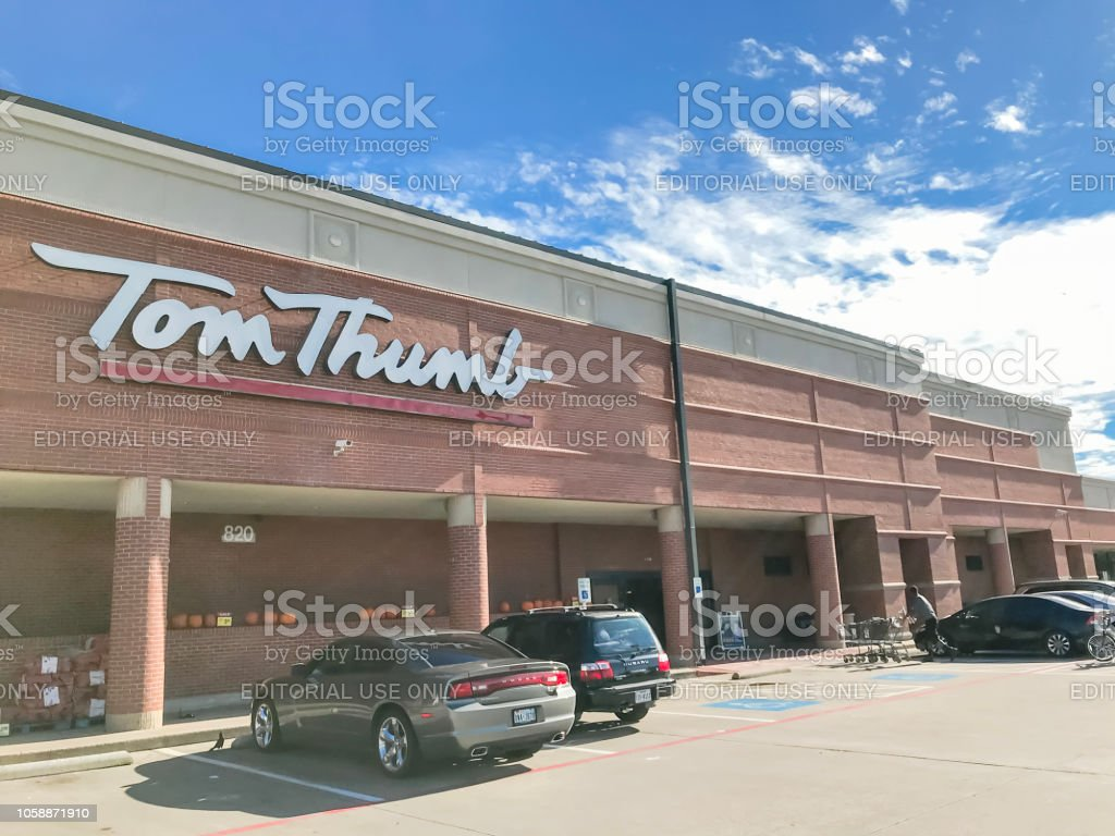 Entrance to Tom Thumb grocery store under cloud blue sky - Stock image .
