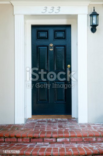 Entrance and black solid wood front door to a traditional house.