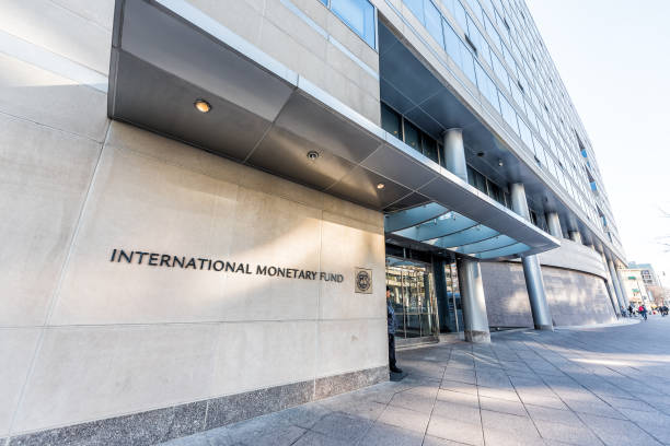 IMF entrance with sign of International Monetary Fund, concrete architecture building wall security guard doors stock photo