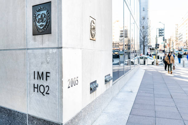 IMF entrance with sign of International Monetary Fund, logo, headquarters 2, two, HQ2 with people walking on sidewalk, street stock photo