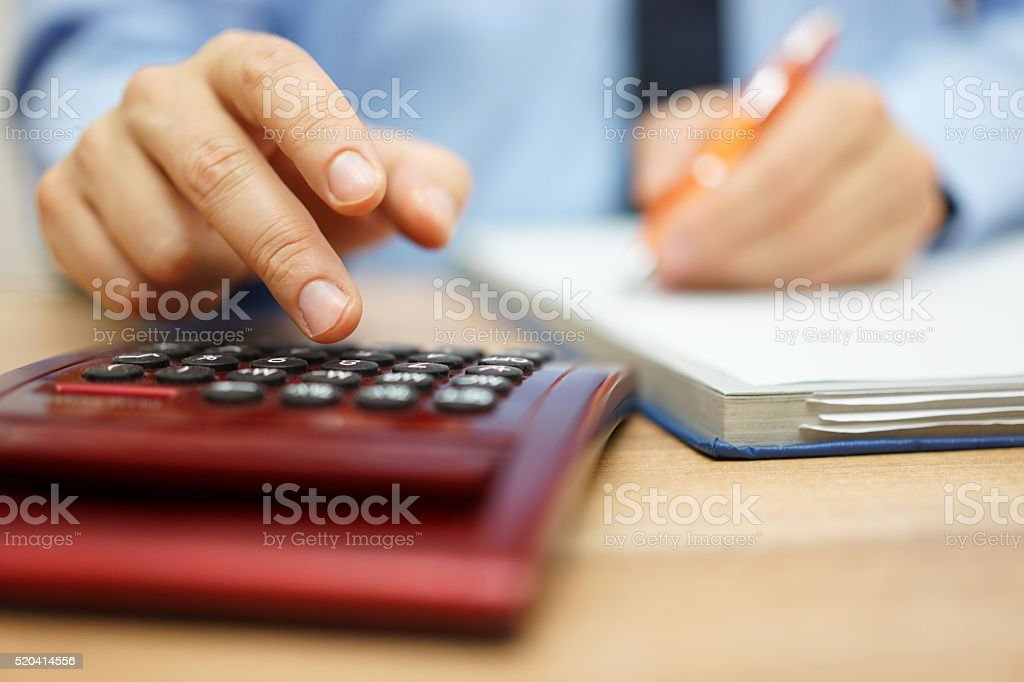 Entrepreneur calculating and reviewing investment plan stock photo
