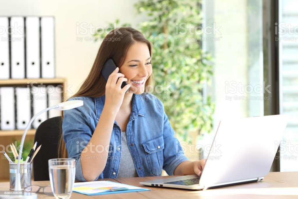 Entrepreneur calling on phone working with laptop stock photo