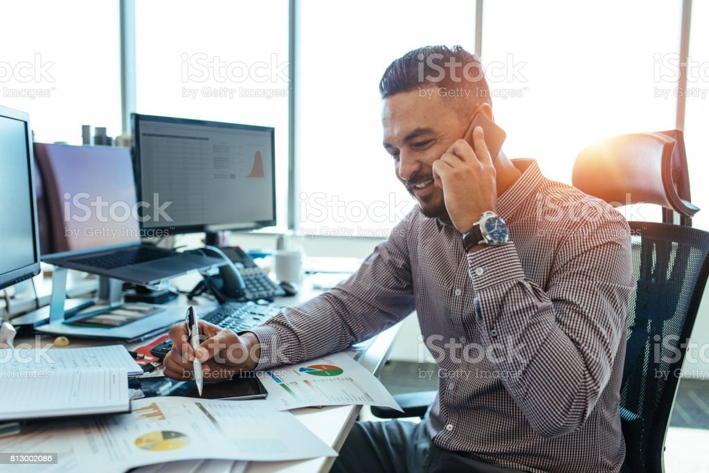 Entrepreneur discussing work over mobile phone sitting at his office desk. stock photo