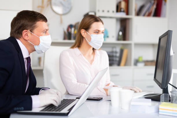 Entrepreneur in medical mask working with female coworker in office stock photo