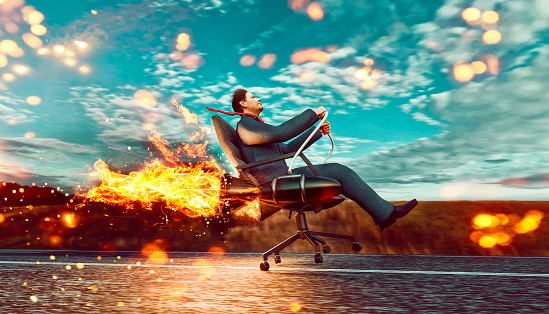 Concept of business growth and success. Man wears business suit and sits in an office chair which is connected to two rockets. He drives the office chair fast on a road and almost takes off.\nNote: The man is a 3D-render with face scan. Model release attached.