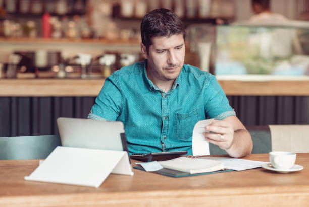 Entrepreneur managing his small business - Businessman looking overwhelmed - Young coffee shop owner going through paperwork stock photo