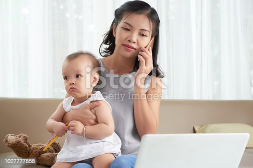 Pretty Vietnamese woman sitting with baby on her laptop and calling on phone