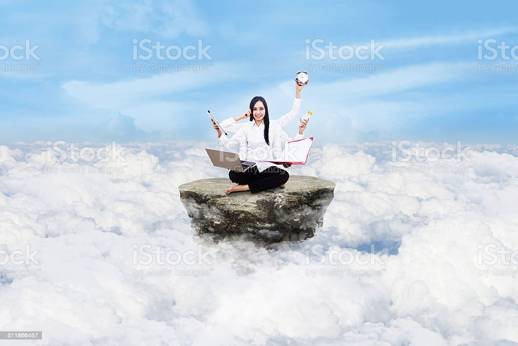 Entrepreneur multitasking above clouds stock photo