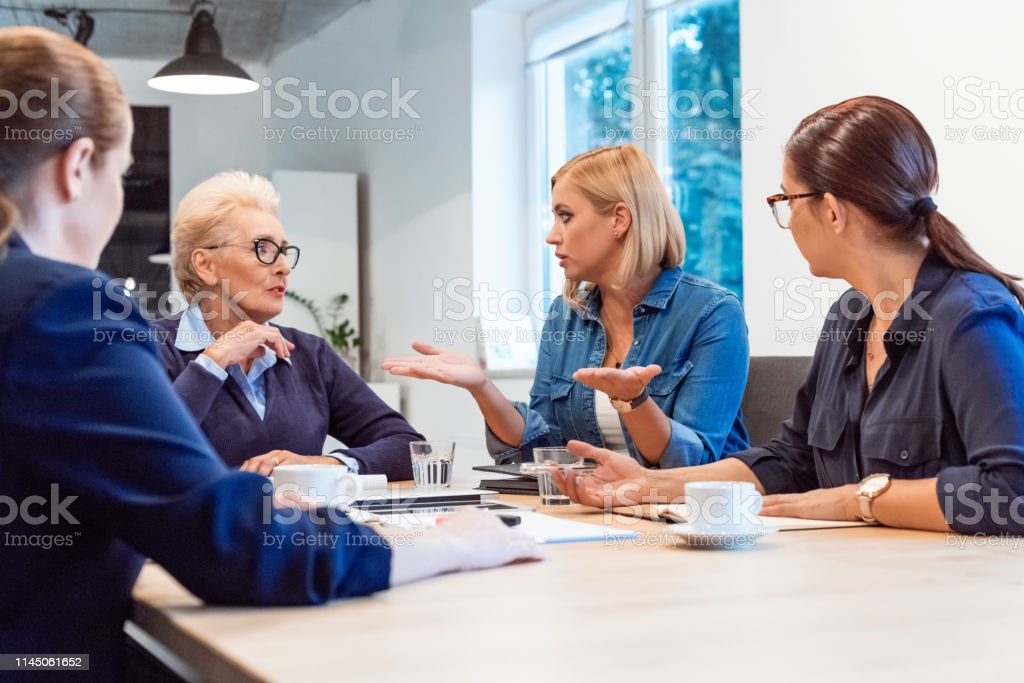 Entrepreneur planning with colleagues in meeting Mature professional discussing new business with colleagues. Confident female executives are working in office. Entrepreneurs are planning strategies. 35-39 Years Stock Photo