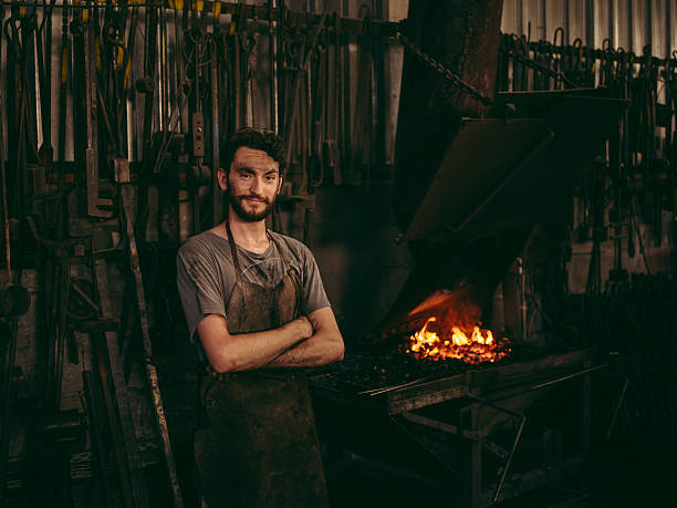 Entrepreneur portrait of blacksmith next to furnace in workshop stock photo
