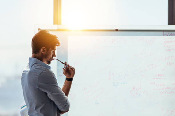 Entrepreneur putting his business ideas on whiteboard in boardroom. stock photo