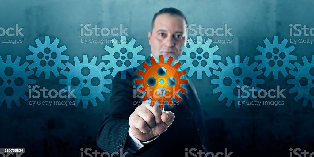 Entrepreneur Selecting A Cog In A Gear Train stock photo