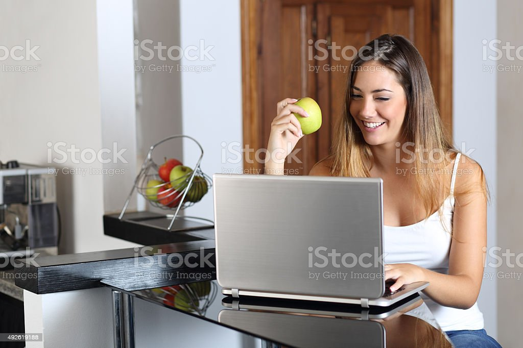 Entrepreneur woman browsing a laptop and eating at home stock photo