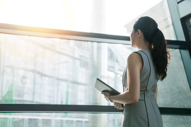 起業家女性が窓の外を見ています。 - 背中 ストックフォトと画像