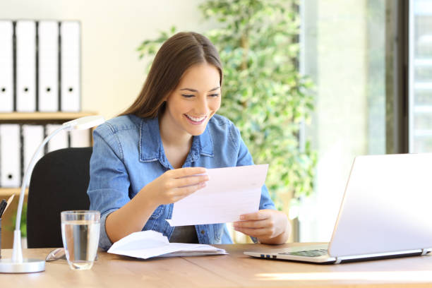 entrepreneur woman reading a letter at office - mail stock photos and pictures
