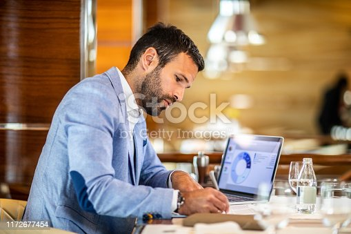 Small business owner filling a document on a clipboard while working in a restaurant. A laptop, glasses, an agenda and a water bottle are on the table.