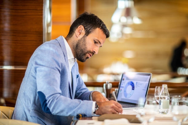 Entrepreneur writing on a document while sitting in a restaurant Small business owner filling a document on a clipboard while working in a restaurant. A laptop, glasses, an agenda and a water bottle are on the table. cash flow stock pictures, royalty-free photos & images