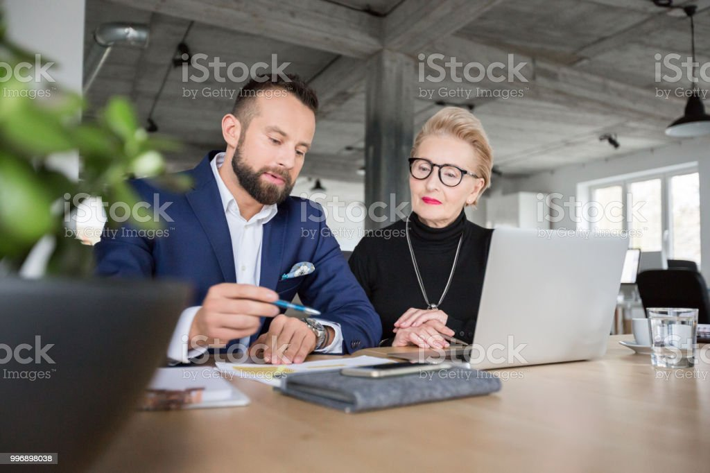 Entrepreneurs discussing new work project Two business colleagues working together. Entrepreneurs discussing new work project sitting in modern office Active Seniors Stock Photo