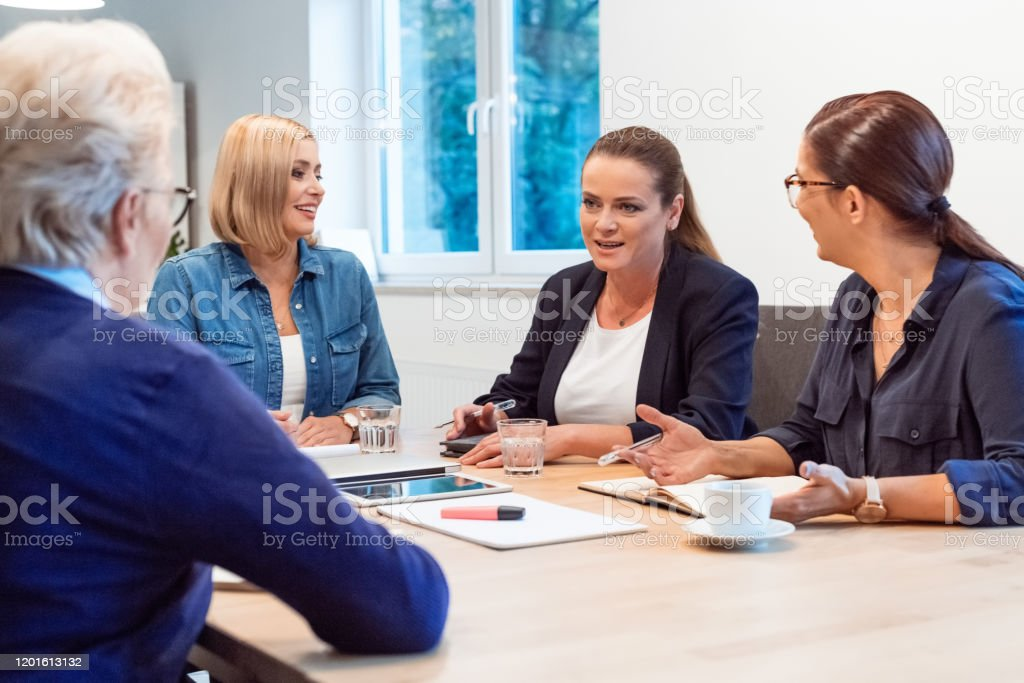 Entrepreneurs discussing with colleagues in office Business professionals planning strategy with colleagues. Female executives are discussing in board room. They are sitting at office. 35-39 Years Stock Photo