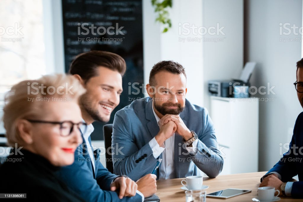 Entrepreneurs planning strategy during meeting Smiling business colleagues looking while sitting at desk during meeting. Design professionals are planning strategy at workplace. They are working at creative office. 30-39 Years Stock Photo