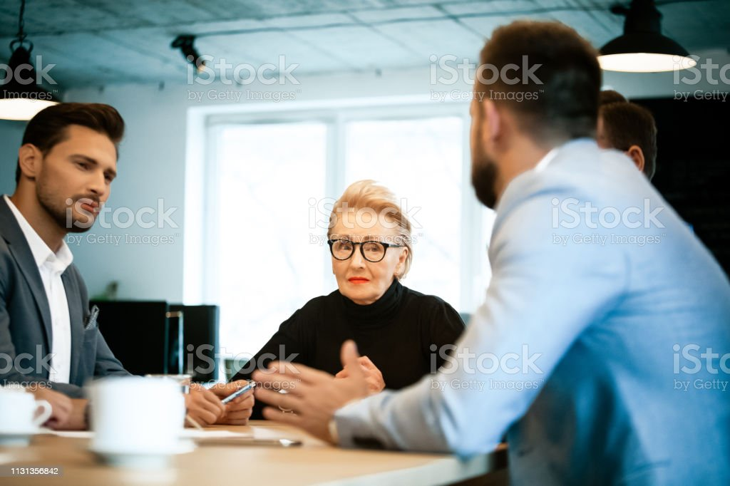 Entrepreneurs planning strategy during meeting Female senior manager discussing with male entrepreneurs during meeting. Colleagues are planning strategy at workplace. They are working at creative office. 30-39 Years Stock Photo
