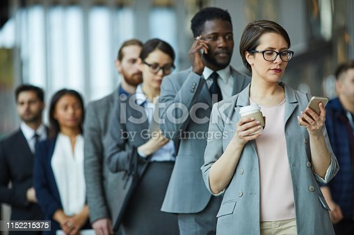 Serious pensive businesswoman with takeout coffee reading news on smartphone while standing in line together with other entrepreneurs