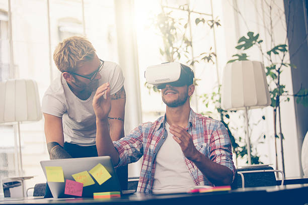 Entrepreneurs testing virtual reality technology with colleague – Foto