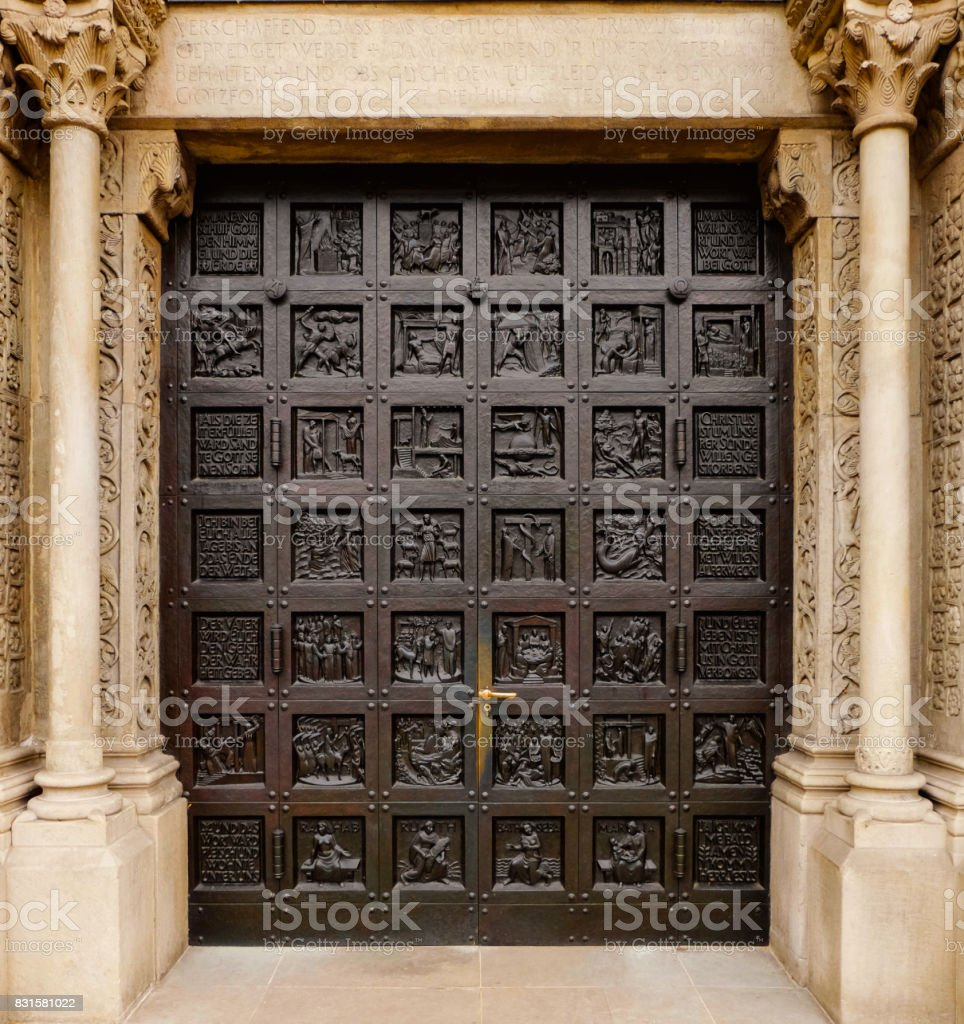 entry door of the protestant Grossmunster church (The Great Minster Cathedral) in Zurich, Switzerland, with religious and symbolic carvings over the whole door stock photo