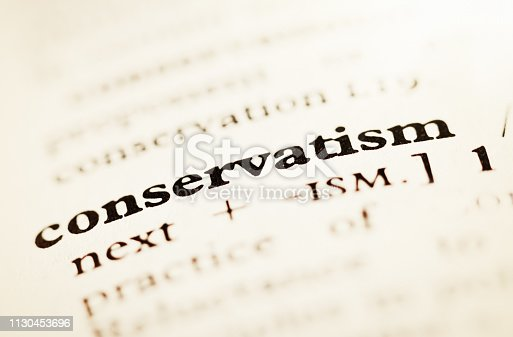 An opened dictionary or encyclopedia shows the entry for Conservatism