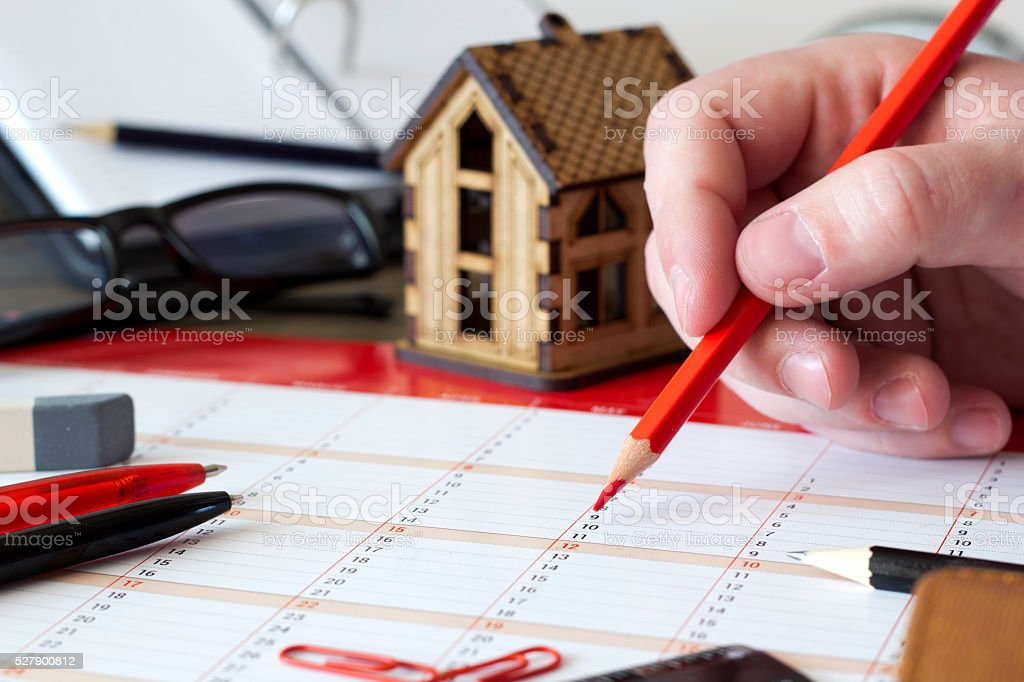 Entry In The Calendar With Pencil Stationery And Small House Stock