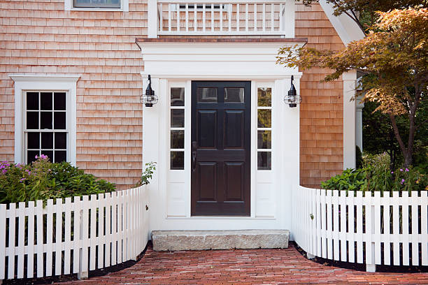 Entryway of brick New England home with picket fence A New England doorway on Cape Cod, Massachusetts in midsummer. front door stock pictures, royalty-free photos & images