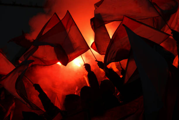 Entusiastic Sport Fans, Pyrotechnic and Flags fans at sports event going crazy, symbol picture for crowd power, enthusiasm, maybe also hooligans and extremism pyrotechnic effects stock pictures, royalty-free photos & images