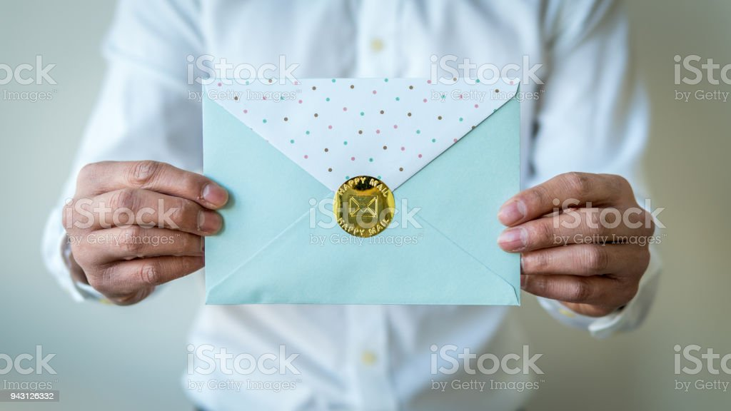 Envelope being held with two male hands stock photo